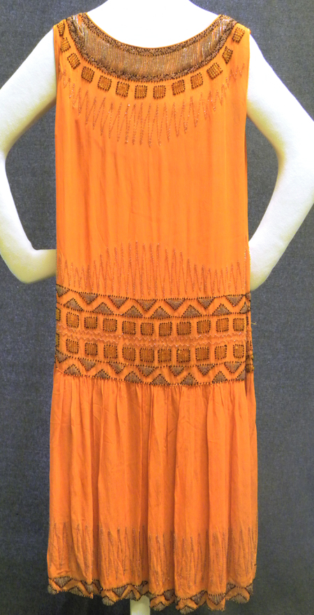 This flapper* dress, though not a Paris design, is hand stitched and beaded, and was collected by Marlyn Lawrentz, a Bloomington resident who adored vintage clothing. She donated it to the Museum in 1996. The circular patterning around the neckline was influenced by beaded collars, like the one pictured below, that were removed from Tut's tomb.