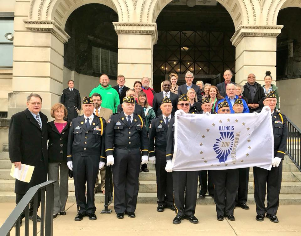 Members of the public, elected officials, and the local American Legion Honor Guard/Color Guard pose with the Illinois Bicentennial flag before the ceremony on Monday, Dec. 4, 2017. (Photo by Candace Summers)