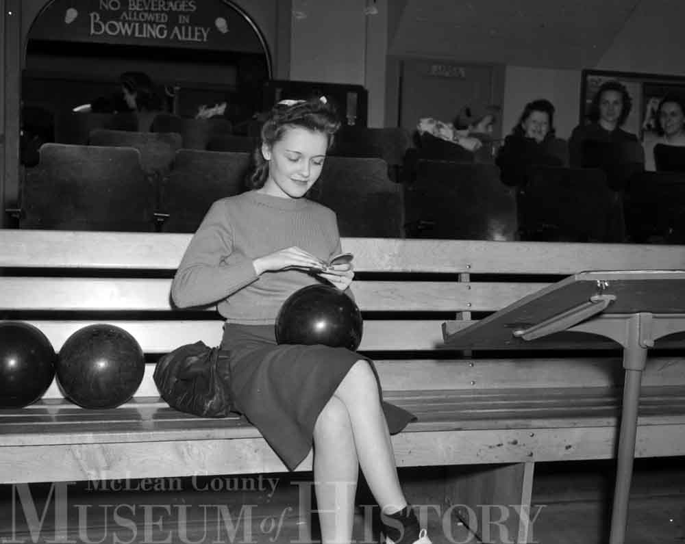 Photo of a woman sitting on a bench with a bowling ball on her lap.