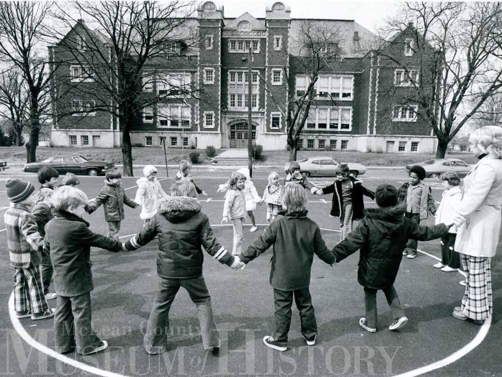 Group of children hold hands in a circle at Emerson School, 1976