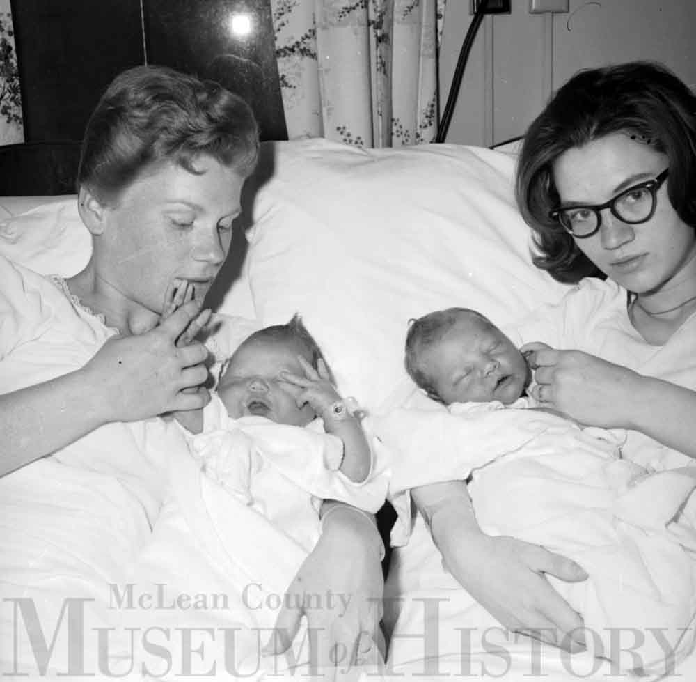 Two women holding their newborn babies, 1965.