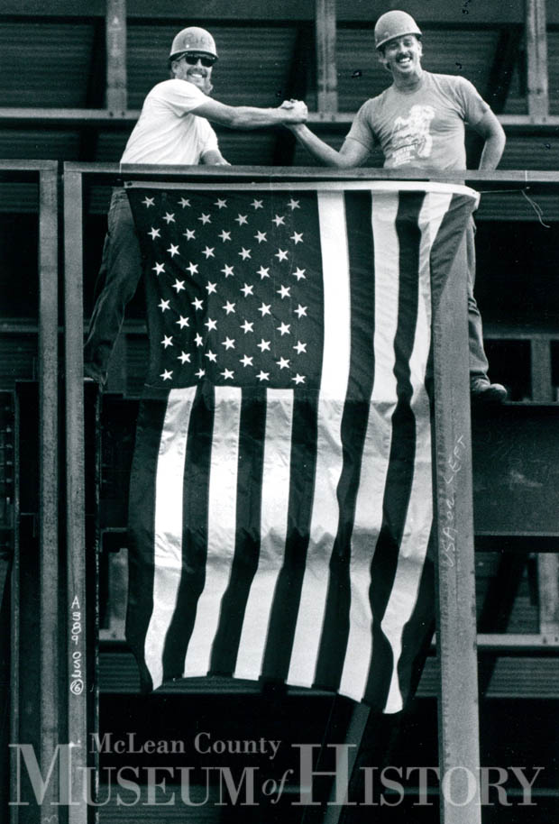 Ironworkers holding a flag, 1990.