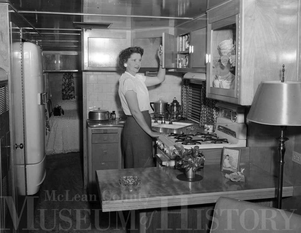 Woman standing in the kitchen of a mobile home, 1953