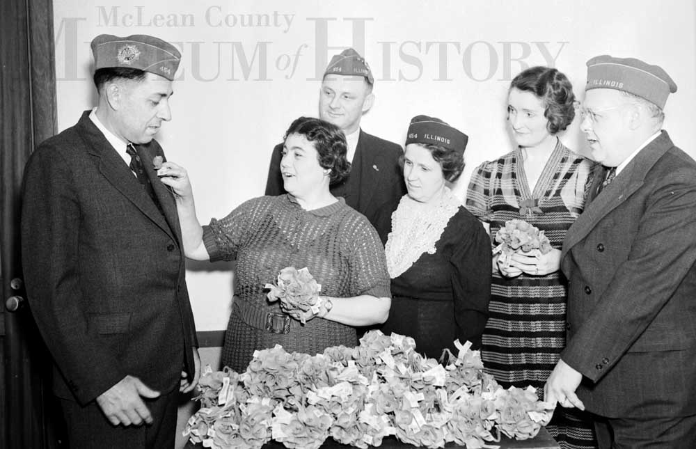 Three men and three women are pictured with a pile of flowers in the foreground. One of the women is pinning a flower to one of the Men's jackets, while the others watch.