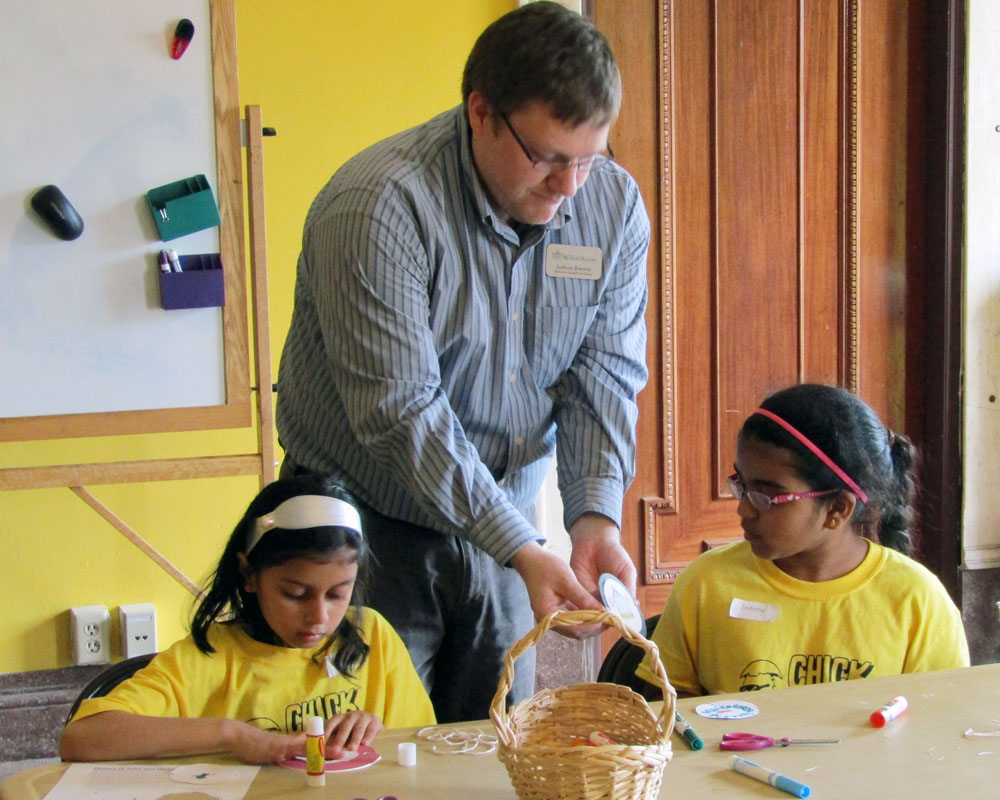 Image of one of our education staff Anthony Bowman helping two students with an educational craft