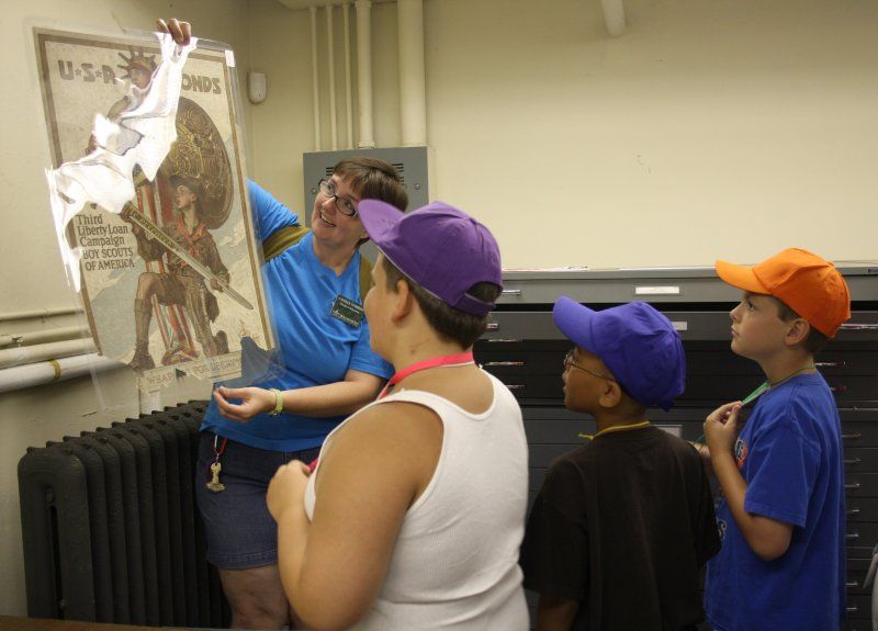 Candace Summers shows day camp students a war bonds poster from the Museum's archival collection.