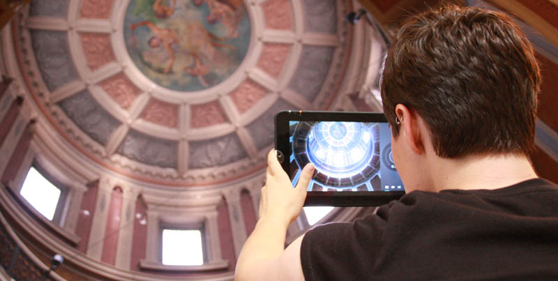 a visitor takes a photo of the dome with her tablet